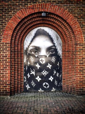 Street art installation by Moroccan born artist Hassan Hajjaj depicting a woman wearing a Louis Vuitton niqab, in Old Street, Shoreditch, London, England.